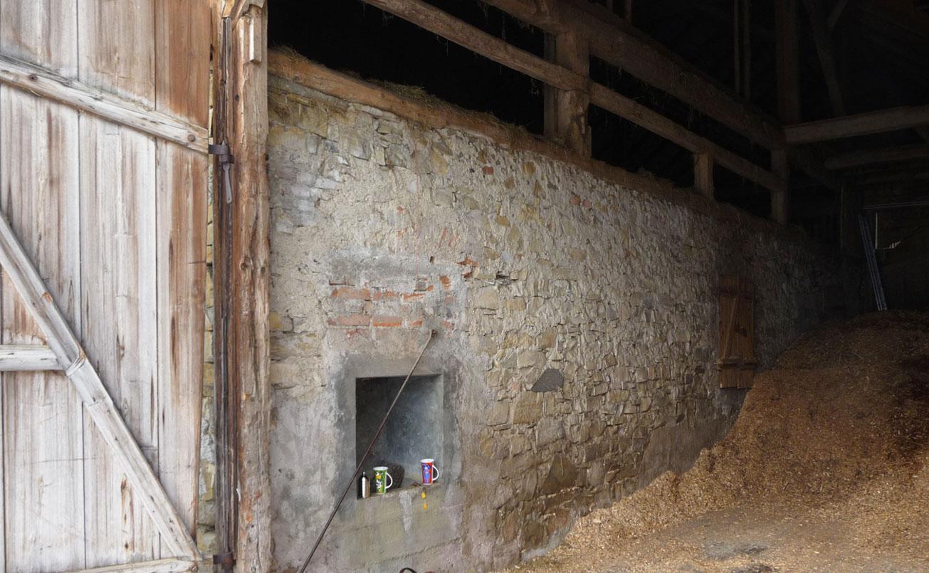 Alte Stallmauer aus Natursteinen unrestauriert. Trennwand von Essraum zu Wohnraum