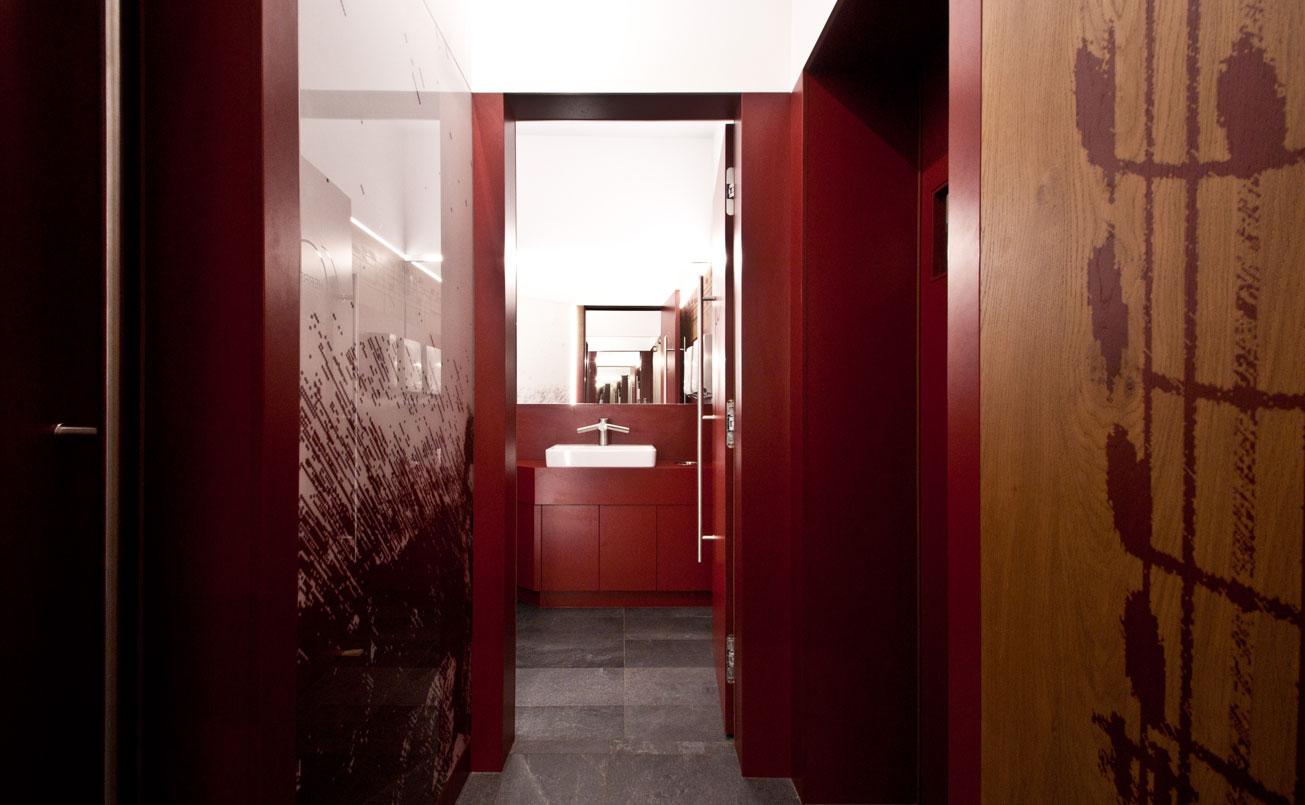 Die Materialien : bordeaurote Kompaktwände, Eichenholz bedruckt, Glas bedruckt und Schiferstein dominieren die Räumlichkeiten.
